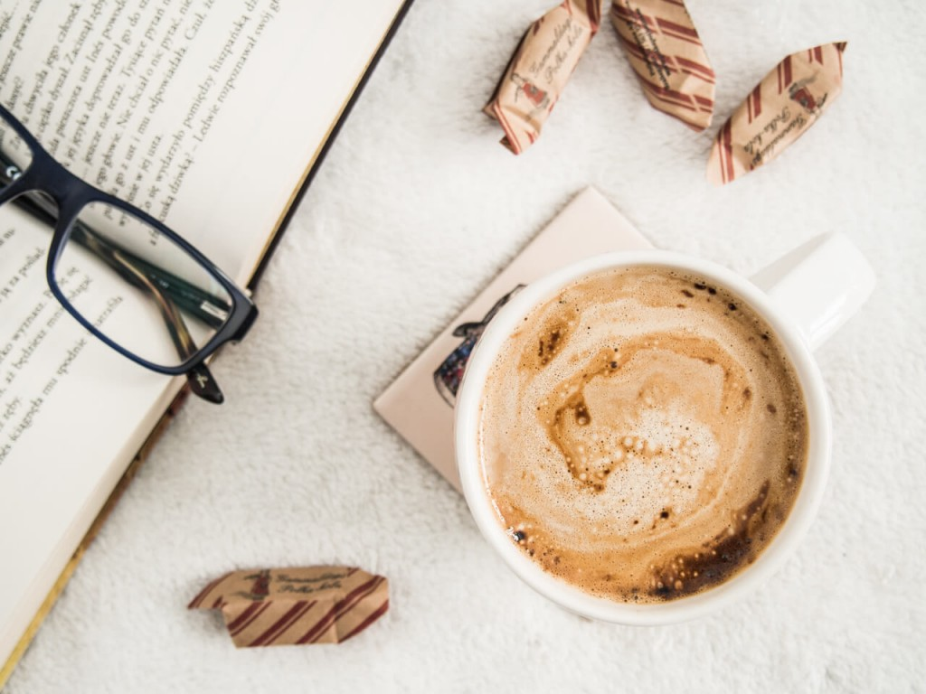 Coffee cup, book, and glasses on a table.