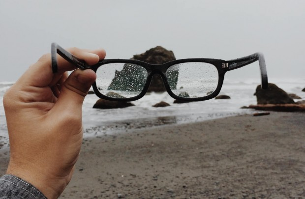 Man holding his glasses while its raining.