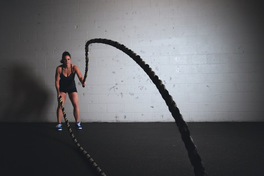 Young woman doing a rope-workout inside a gym