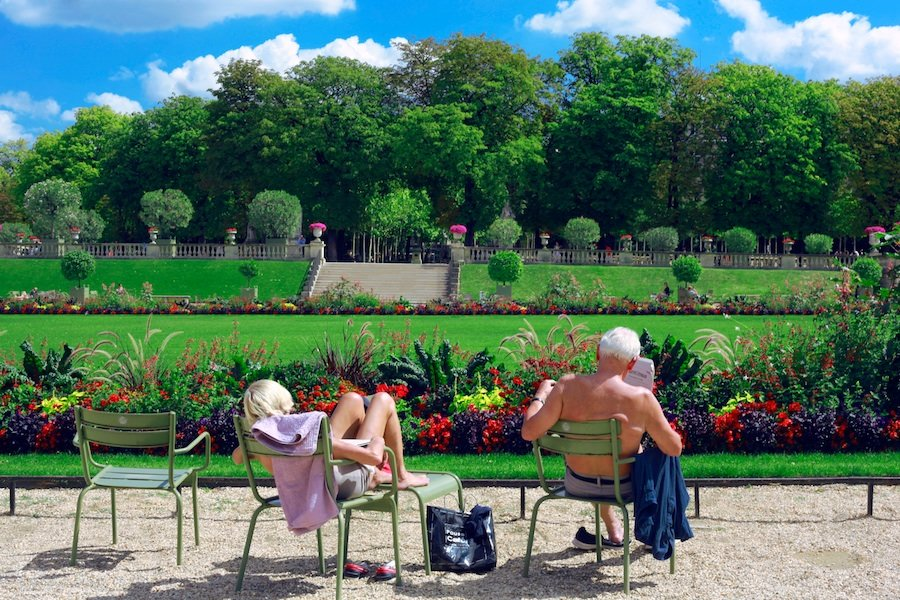 Elderly man and woman reading newspapers while bathing in the sun
