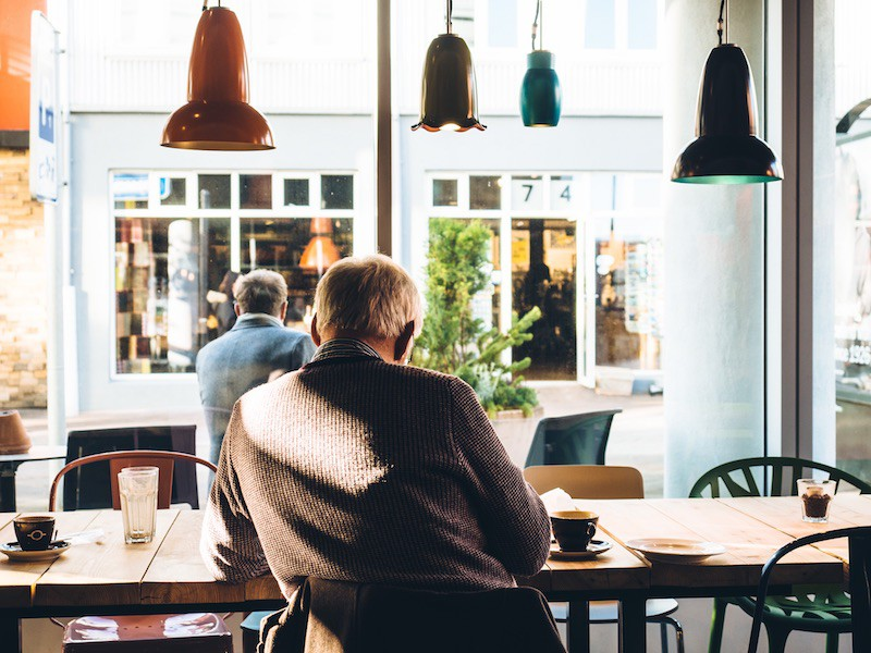 Old man sitting inside a cafe during noon