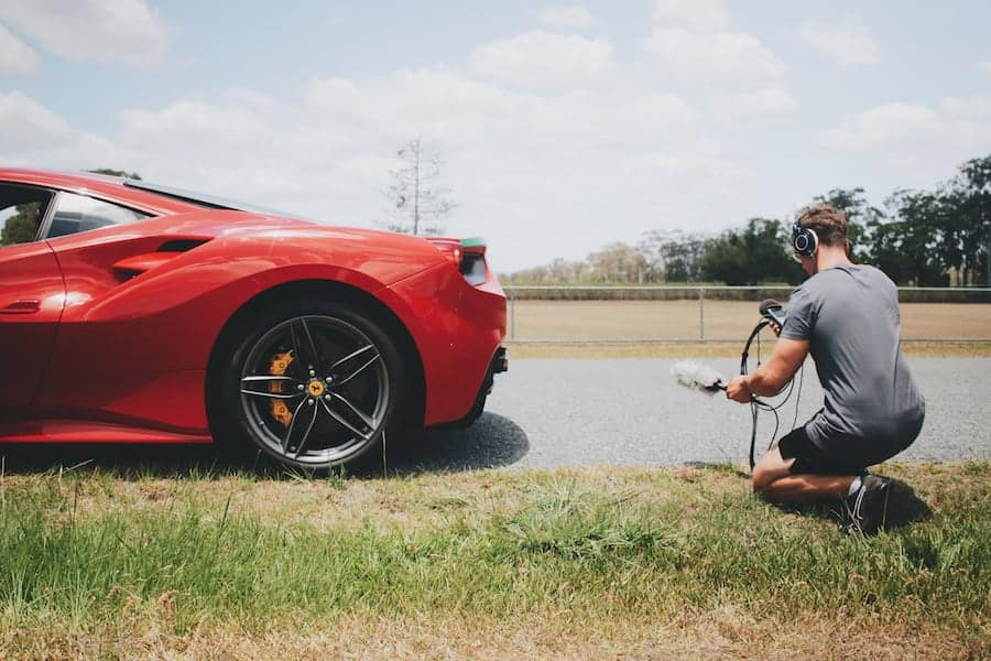 man recording audio of a ferarri car