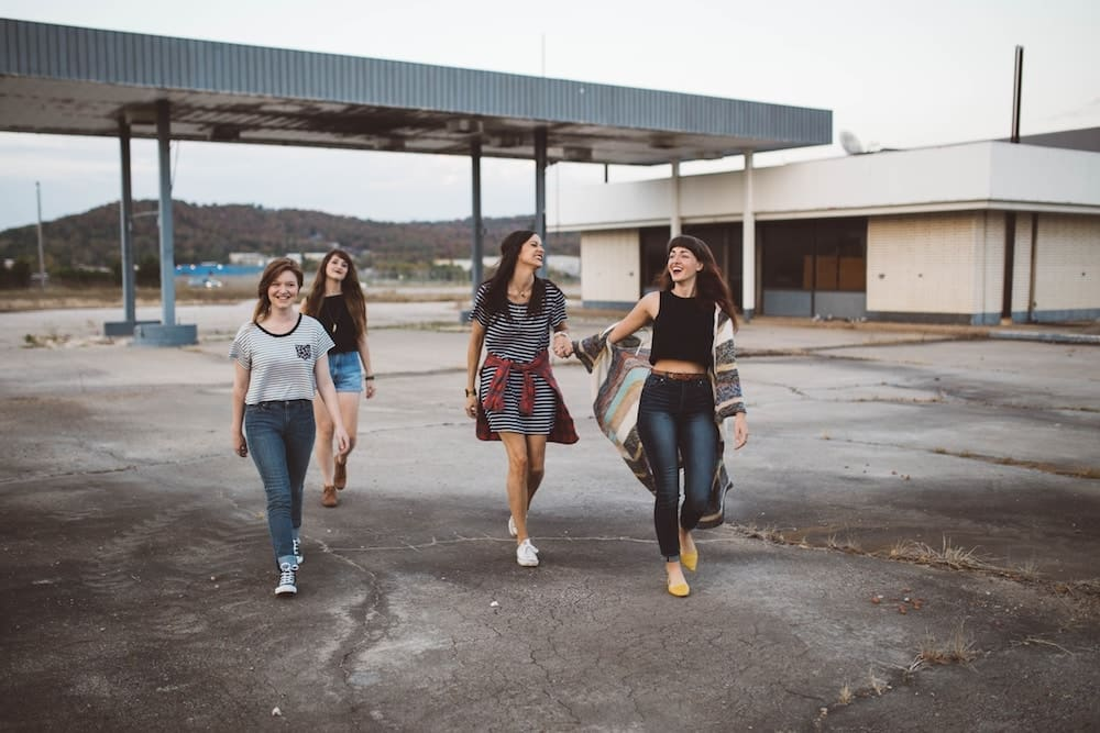 Four girl friends walking together and laughing