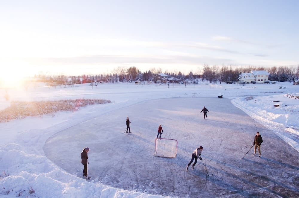 Group of Friends playing ice hockey on a cold winter day in canada