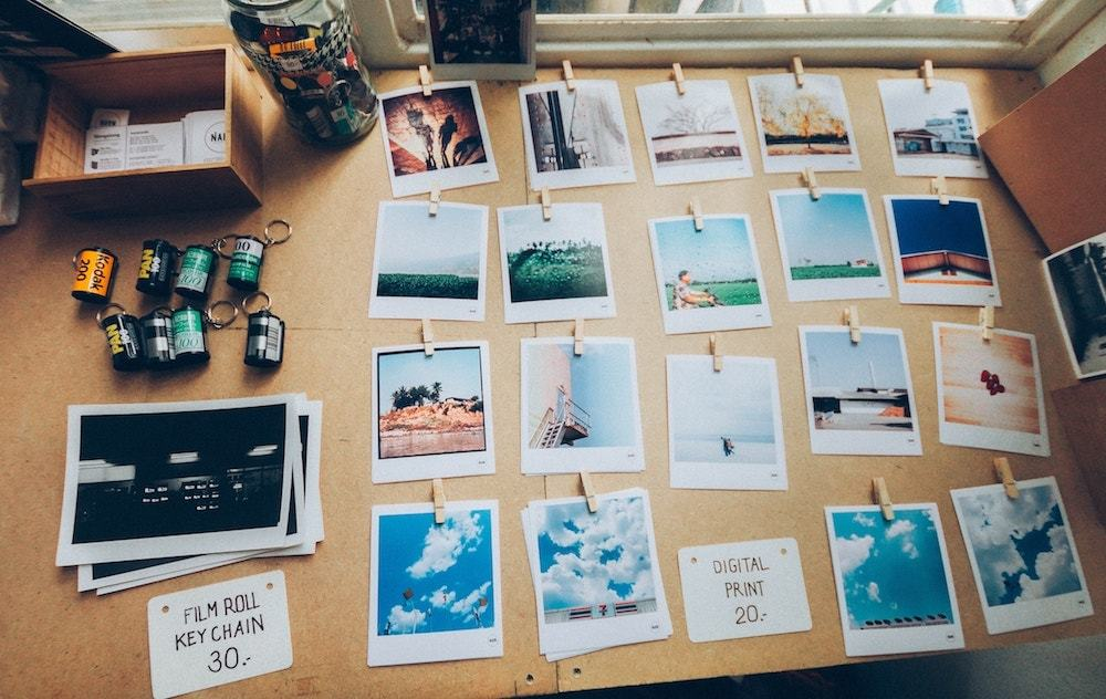 Printed polaroid pictures neatly organized on a wooden desk