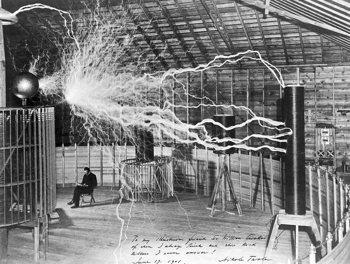 Tesla sitting next to his magnifying transmitter generating millions of volts
