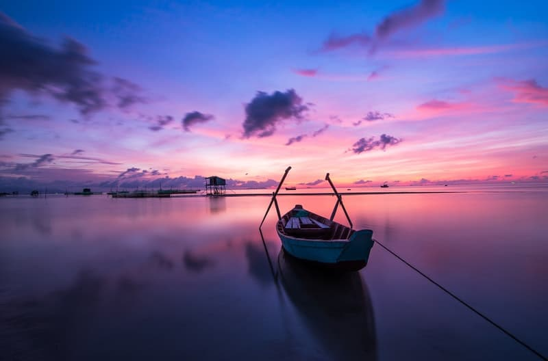 Docked wooden boat on a lake with purple skies behind it