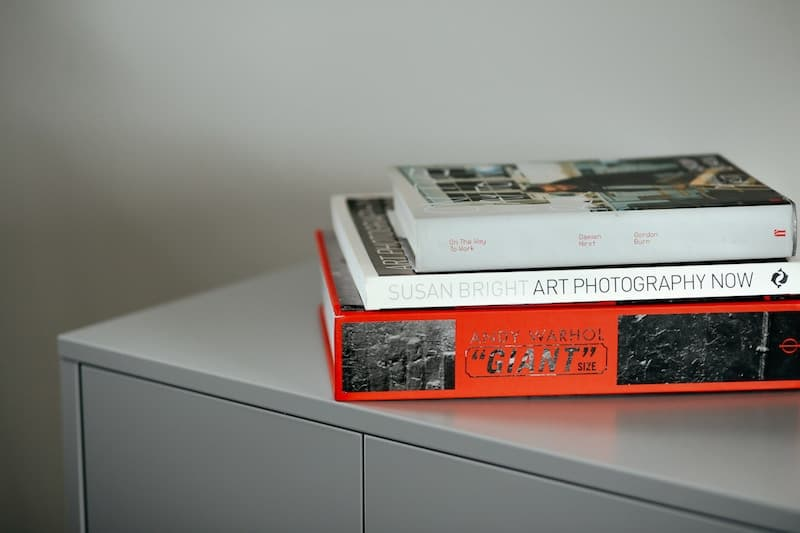 Three books stacked on top of each other on a grey file cabinet