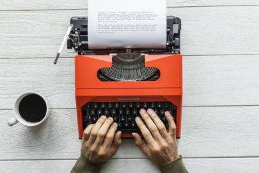 Man typing on a red vintage typewriter-min
