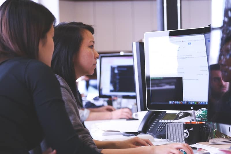 Two women working together on a project at the office
