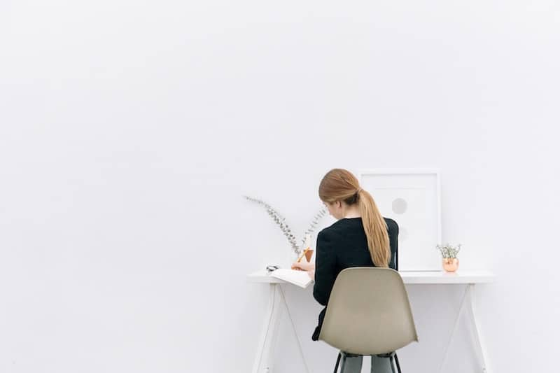 Young woman working behind a minimal desk