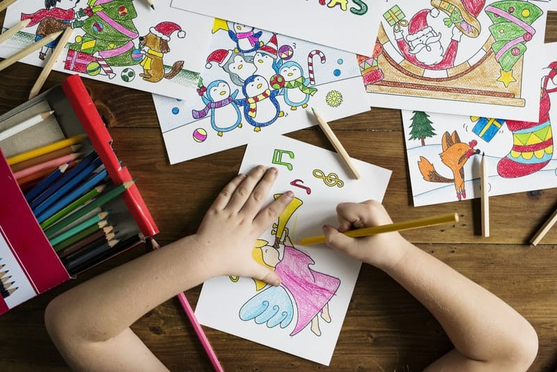 top-angle-photo-of-child-holding-pencil-while-drawing-female-angel-playing-wind-instrument