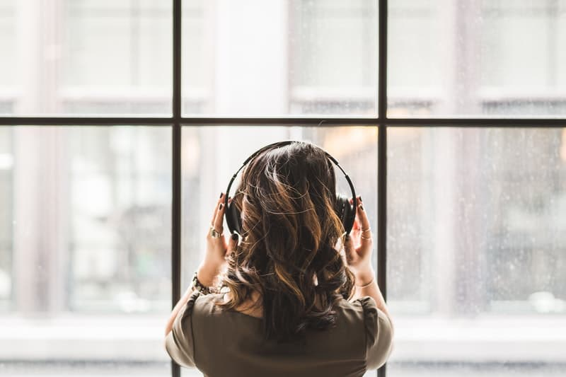 Beautiful Woman Looking out into the window while listening to music