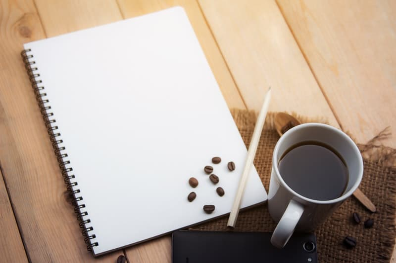 black coffee and a notepad laying on top of the breakfast table