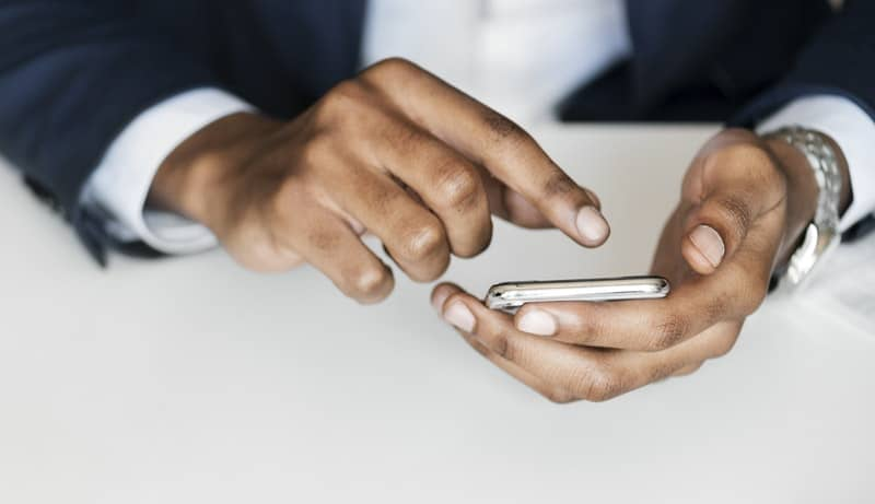 man in black suit holding smartphone