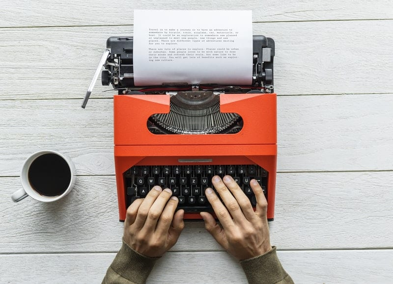 person typing on a vintage orange typewriter