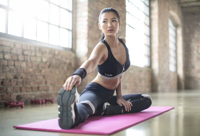 woman-in-black-sports-brassiered-and-black-pants-doing-yoga