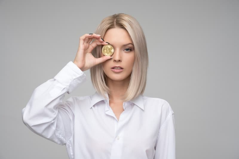 attractive young woman holding up a bitcoin coin