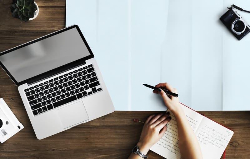 person holding pen near macbook pro