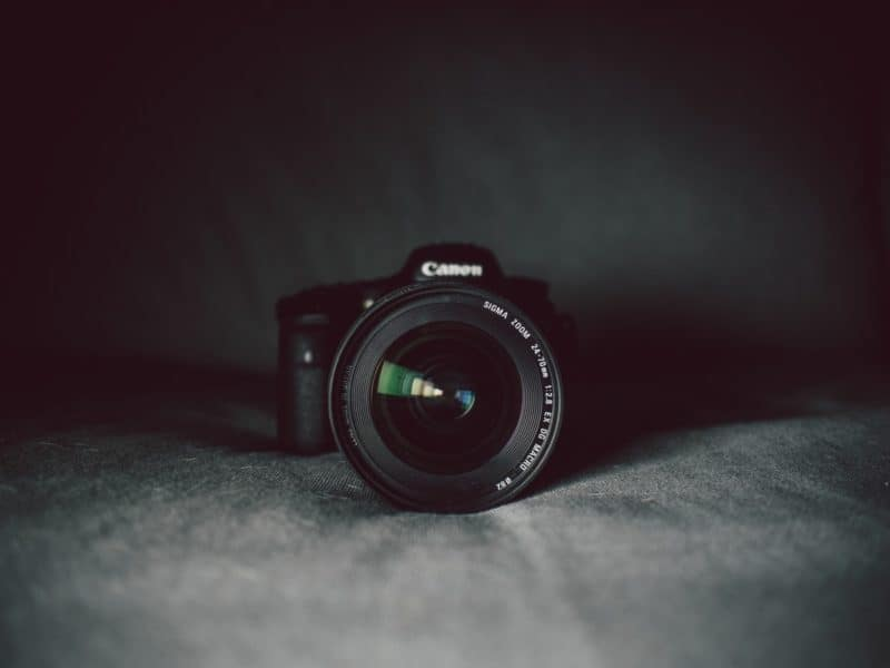 Canon camera with a sigma zoom lens laying on a sofa