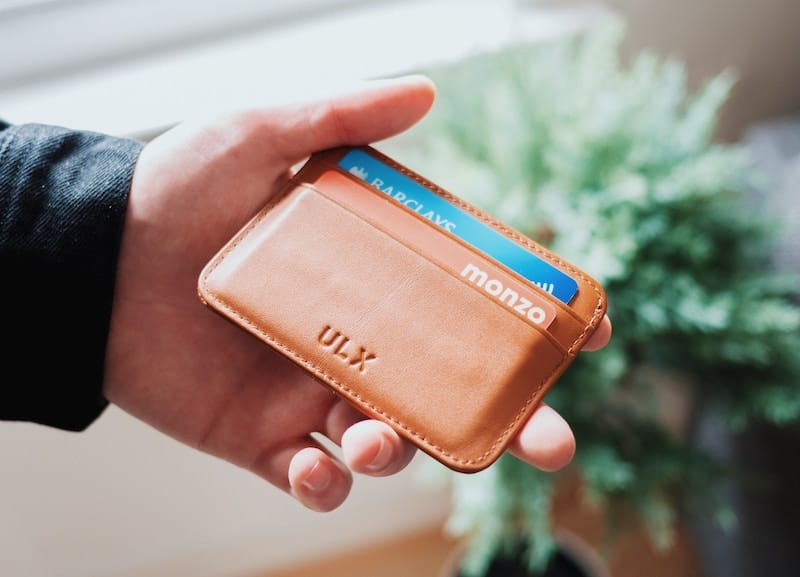 Man holding a classy leather wallet with credit cards inside