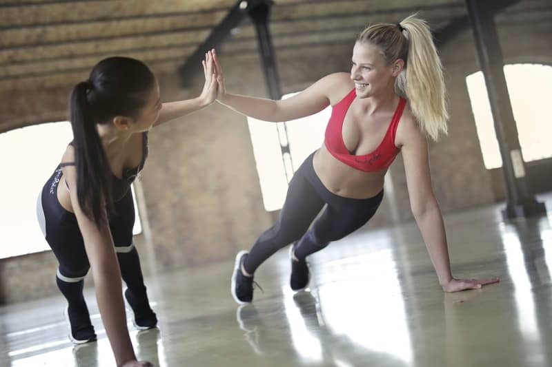 Two Women Exercising Inside a Modern Gym