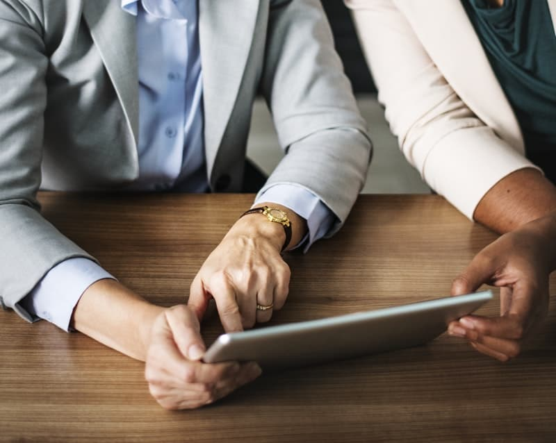 Two people going over their businees plan on a mobile tablet