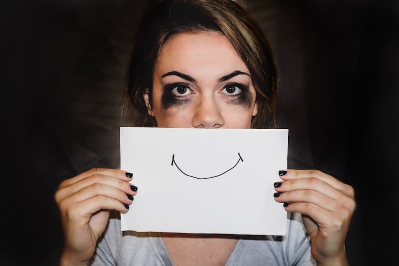 Unhappy Woman Holding up a Drawing of a Smile Face