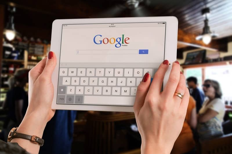 person holding an ipad with google homepage