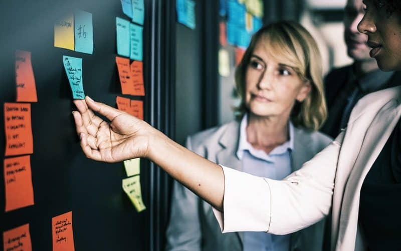 womna holding sticky notes at a business meeting