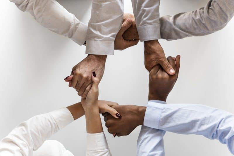 Four office people uniting hands