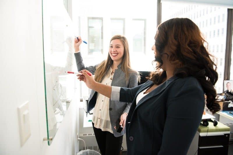 Two Women Writing on Dry Erase Board