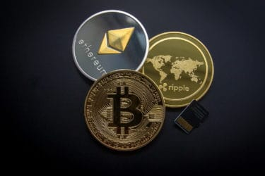 physical cryptocurrency coins against a black background-min