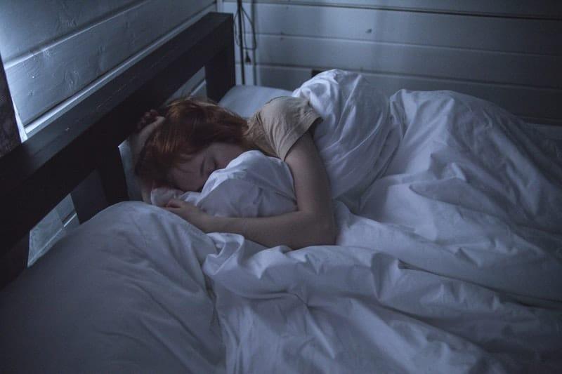 woman sleeping in a dark blue room