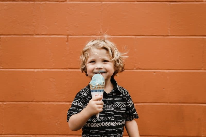 Cute Kid eating ice cream against an orange background