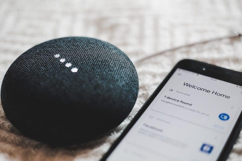 Google home device next to smartphone