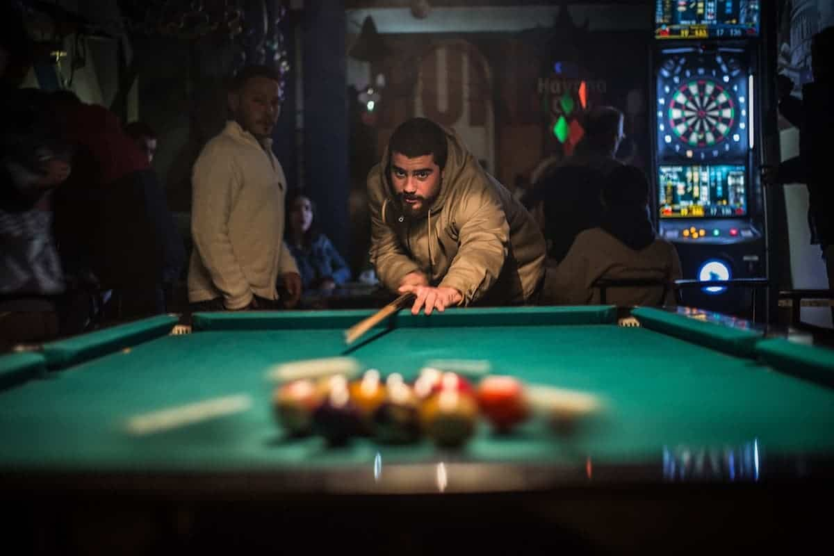 Man Breaking in Pool inside a small bar at night
