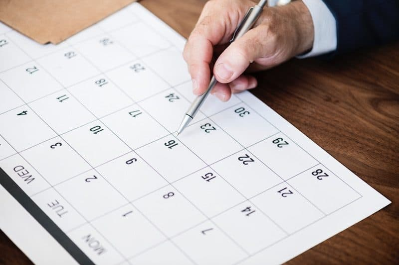 Man Looking over a calendar to see what is scheduled