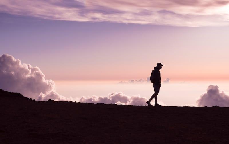 Man Walking on top of a mountain during sunset