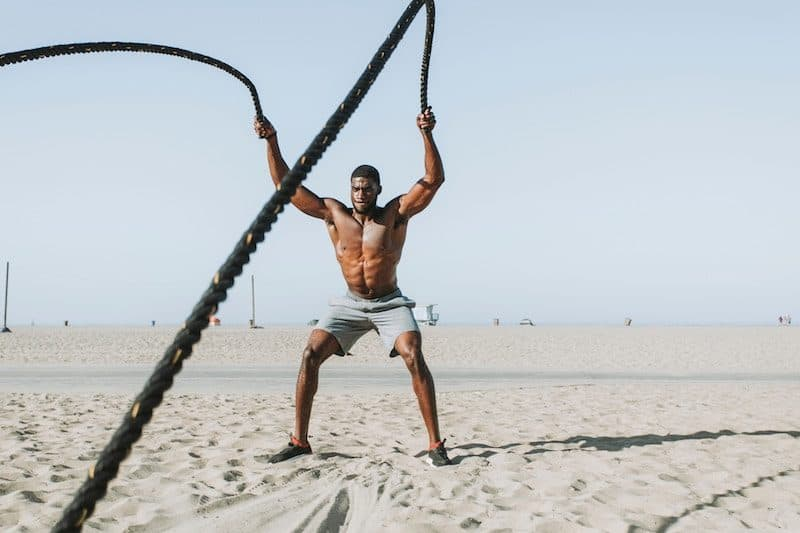 Man doing rope workouts at the beach during noon
