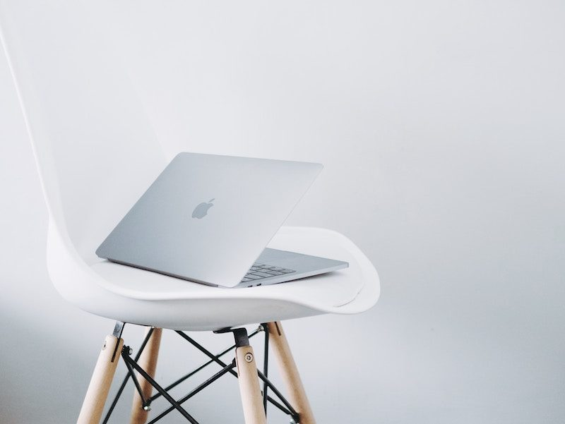 Silver Macbook Pro Sitting on a White Chair