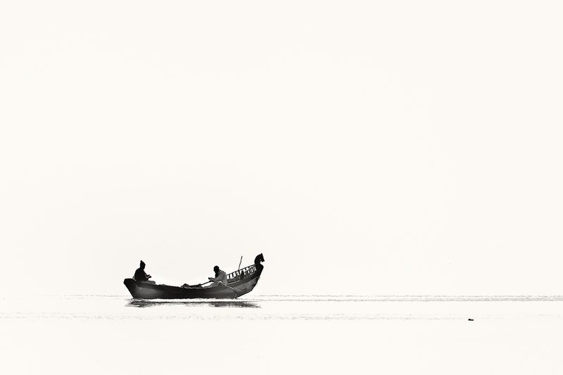 Two Person Riding Boat on Body of Water