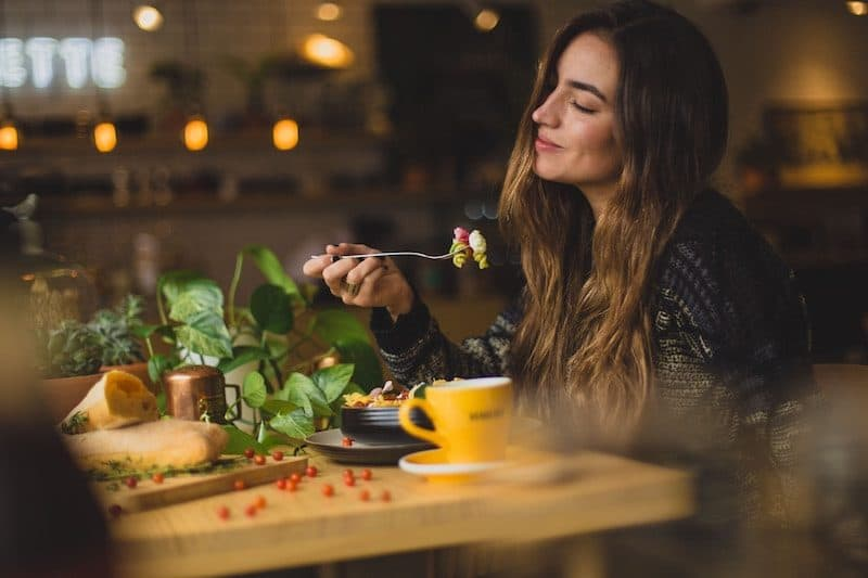 Woman Eating a freshly made meal inside a restaurant