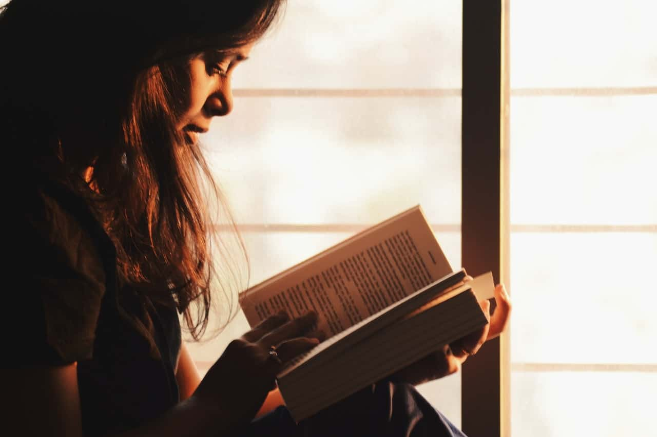 Woman reading her favorite book near a window