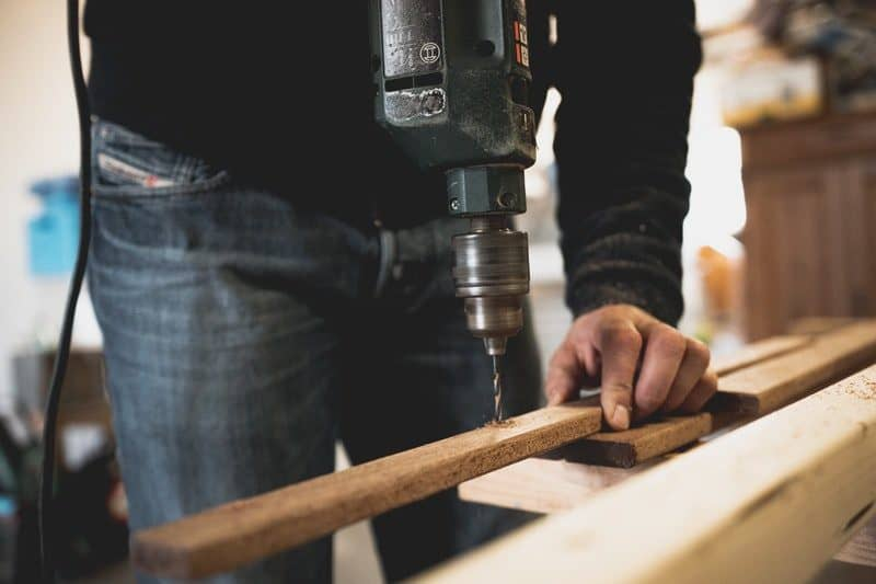 man drilling a hole in a piece of wood