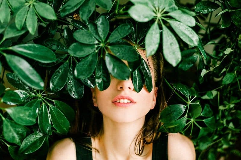 woman hiding her eyes behind a green plant