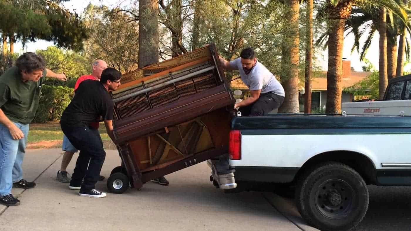 Four men moving a piano