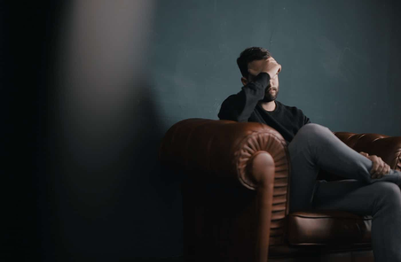 Stressed man sitting on a sofa chair
