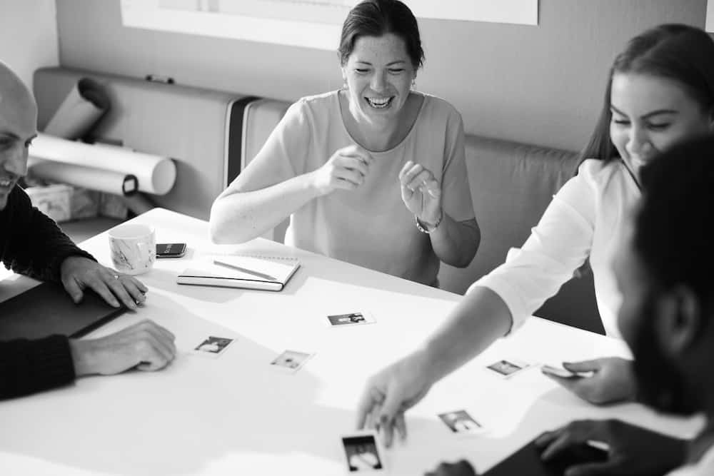 grayscale photo of two men and two women playing cards on table white laughing
