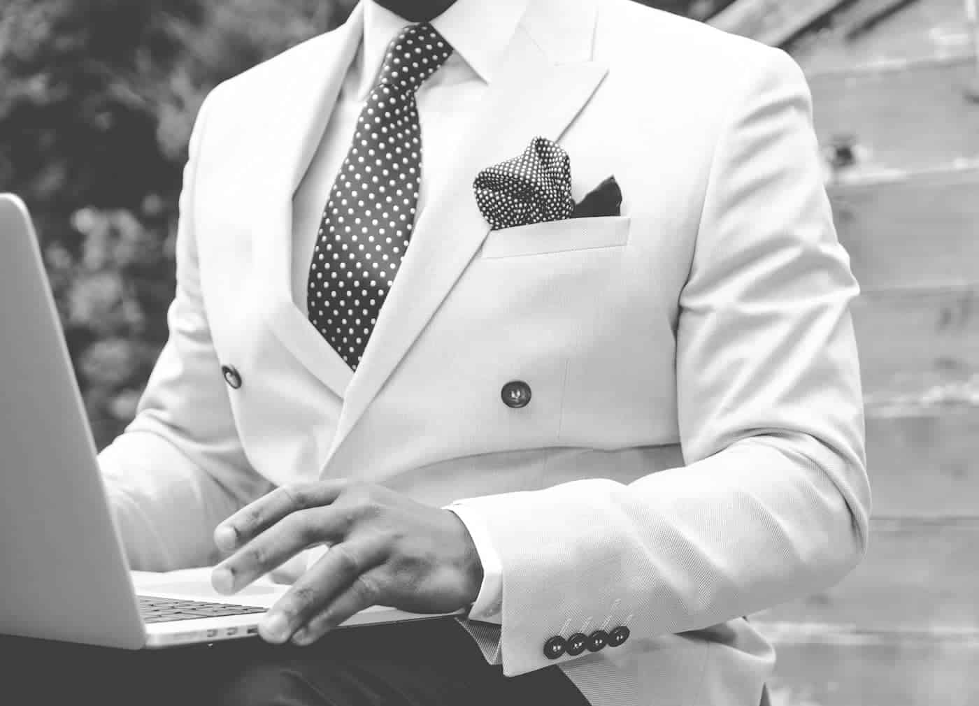 man in white suit working on his laptop